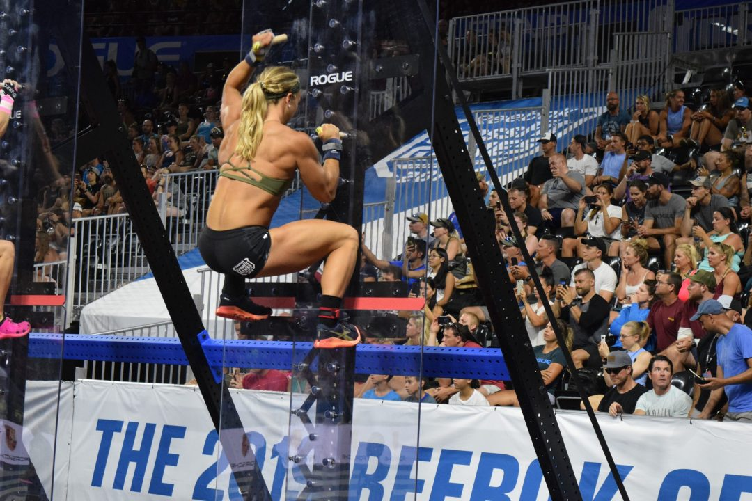 Amanda Barnhart climbs a pegboard in the Coliseum at the 2019 CrossFit Games