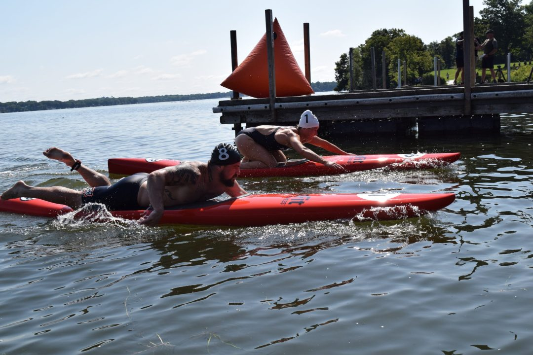 Matt Mcleod and Tia-Clair Toomey approach the finish line of the Swim Paddle event at the 2019 CrossFit Games