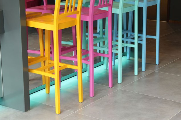 Colourful light detail and accompanying stools at the bar.
