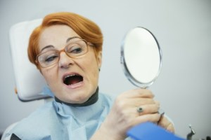 woman looks at teeth in mirror