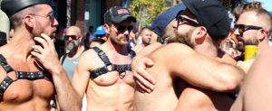 Gay men at pride parade in fetish wear harness