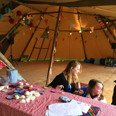 Face painter painting children's faces at party in Tipi