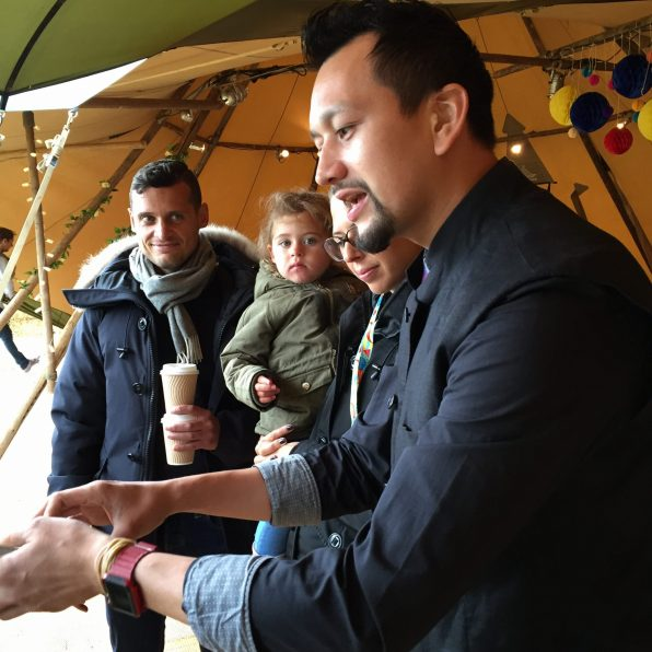 Hand Magicians doing tricks for family at outdoor event