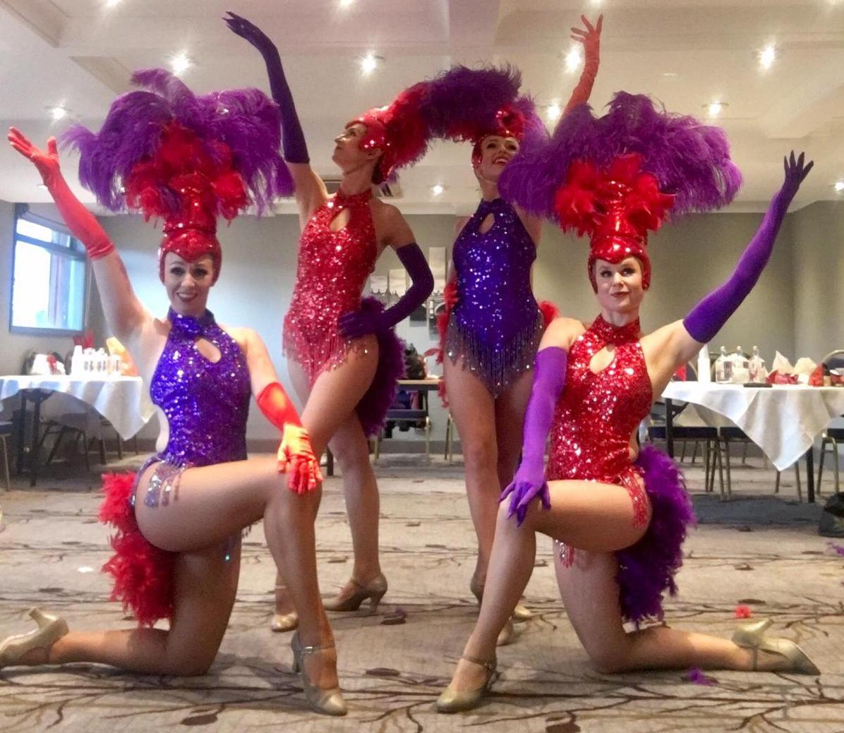 Showgirls in red and purple feathered and sequin costumes