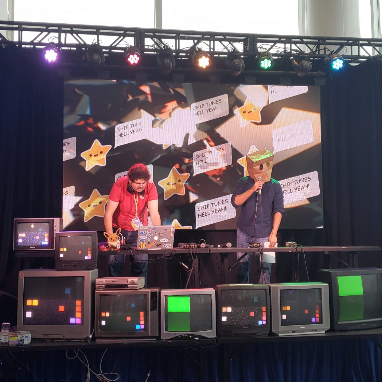 A stage at the Magfest chiptune area. There's a bunch of CRTs with pixel images on them. This area had a signup sheet and any chiptune based musicians could play. I played a set myself!