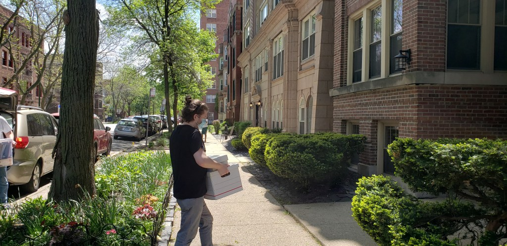 My boyfriend carrying a box into an apartment buidling. A minivan with it's backdoor open on the left.