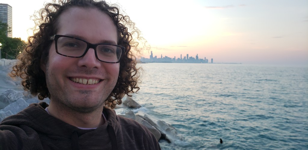 Selfie in front of the lake! You can see the sun setting behind the city skyline behind me. I could use a shave but I look full of adventure.