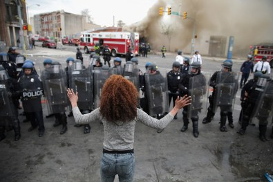 A woman faces down a line of Baltimore Police officers in riot gear during violent protests following the funeral of Freddie Gray April 27, 2015.