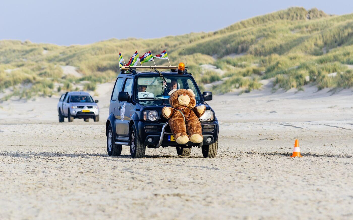 Auto van de organisatie met een knuffelbeer voor op de bumper.