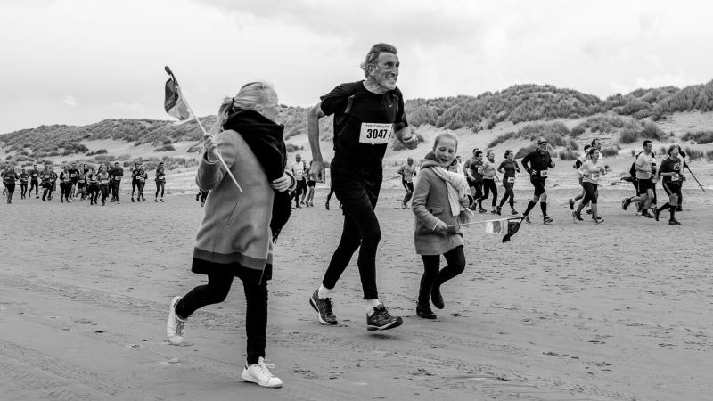 Berenloper met meelopende supporters op het strand tijdens de halve marathon van de Berenloop 2017.