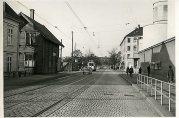 Fjøsangerveien med den nedlagte jernbanestasjonen til venstre i bildet. I bygningen foran var en filial av Nygårds handelsforening. På motsatt side ligger Forum kino. Fotograf ukjent. Arkivet etter Reguleringsvesenet.
