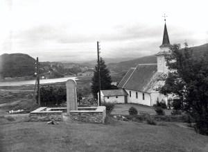 Åsane med gamle Åsane kirke i 1957. Fotograf: Nils Selvik. Arkivet etter Bergens Arbeiderblad/Bergensavisen, Bergen Byarkiv.