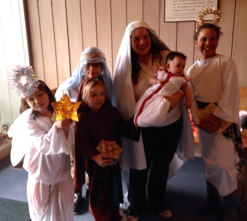 Costumed children with mother and baby gather in meetinghouse lobby