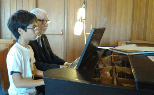 A young and an old musician at the keyboard