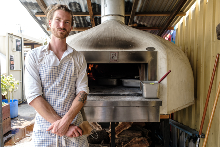 June's Pizza owner Craig Murli in front of his pizza oven. June's Pizza is one of several zero waste businesses that make up the eco industrial yard 0saa Complex. Started by Craig Murli, June's specializes in pizza dough made with Type 85 flour and tops its pizzas with ingredients from Gomez farms and Offbeat Farms. September 2, 2020. Photo: Pete Rosos