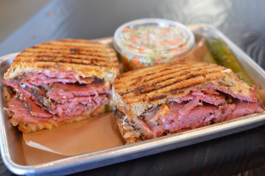 A metal tray lined with butcher paper holds a pressed Reuben sandwich cut in a half and a plastic container of coleslaw.