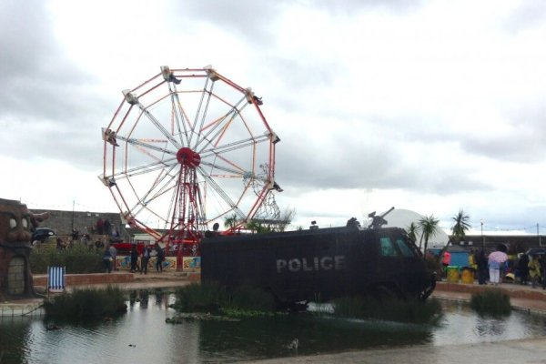 Dismaland's Ferris Wheel seen from across the pool.