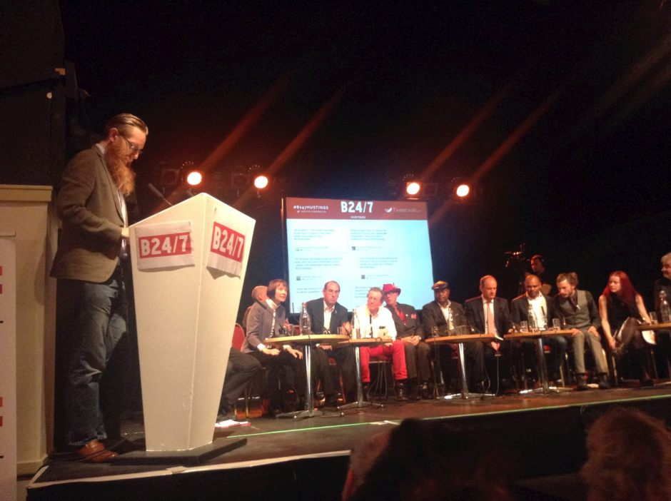 Twelve of the thirteen mayoral candidates pictured (in part, at least) at the Bristol 24/7 hustings. From left to right: Martin Booth (editor of Bristol 24/7, standing, not a candidate); Tom Baldwin's legs; Kay Barnard; Tony Britt's head; Tony Dyer; George Ferguson; Stoney Garnett; Mayor Festus Kudehinbu; Charles Lucas; Marvin Rees; Paul Saville; Christine Townsend; Paul Turner's head and shoulder. John Langley had to leave early. Photo by Iain Walker