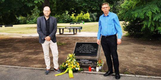 BVV-Chef Groos und stellvertretender Bezirksbürgermeister Klemm stehen am Gedenkstein für den Schiffbruch im Hafen von Treptow