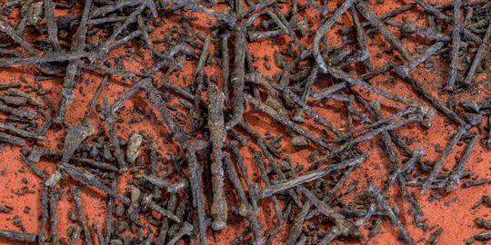 viele verrostete Nägel liegen auf rotem Sand