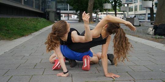 Zwei Frauen posieren auf einem Bürgersteig aneinander gefesselt.