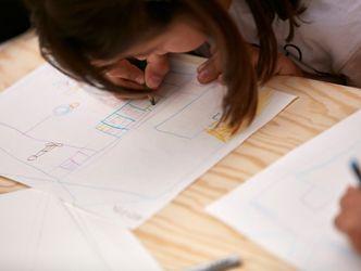 Ein Mädchen malt mit Buntstiften auf ein Blatt Papier.