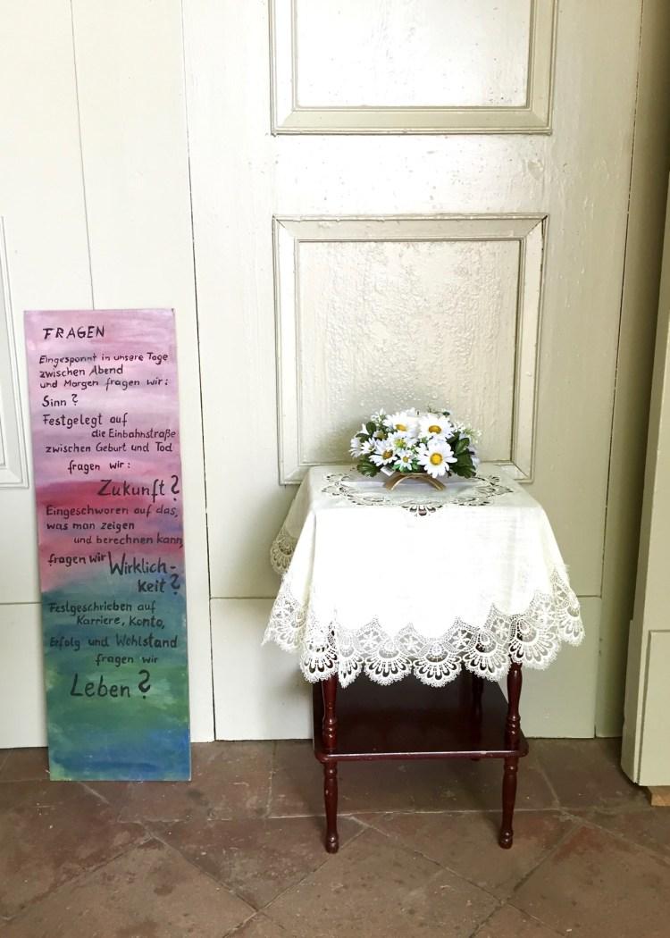 Plastikblumen und Fragen an den Kirchenbesucher teilen sich den Eingangsbereich der Kirche.