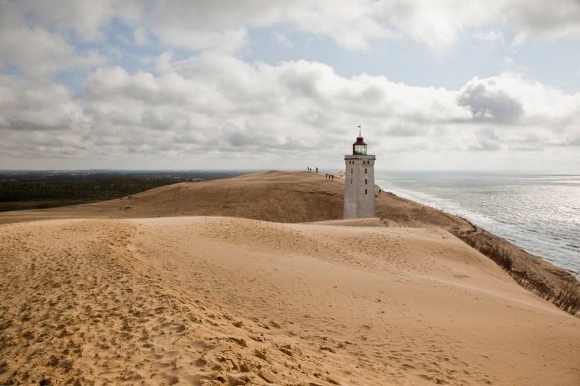 Dänemark, Nordseeküste: Im Hintergrund der Leuchtturm Rubjerg Knude Fyr, der von der Düne halb versandet ist und in den nächsten Jahren von der Klippe ins Meer zu stürzen droht.