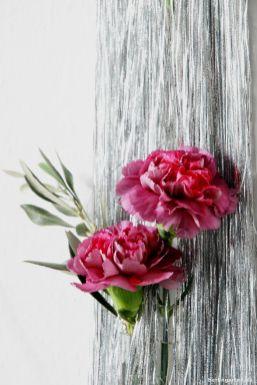 Wunderschöne rot-rosa Nelken lugen aus dem Lametta hervor