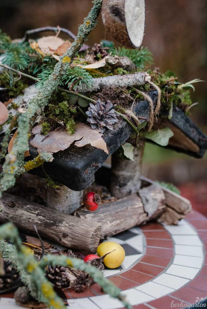 Das Vogelhaus ist mit Moos, Zapfen und Blättern geschmückt