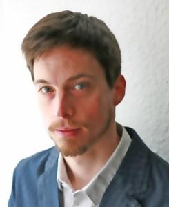 Ein Mann mit braunen Haaren, blauen Augen, Bart und Schnurrbart und trägt einen blauen Anzug in die Kamera mit einem freundlichen Ausdruck.
