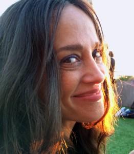 Eine Frau mit langen braunen Haaren und braunen Augen schaut seitlich in die Kamera und lächelt.