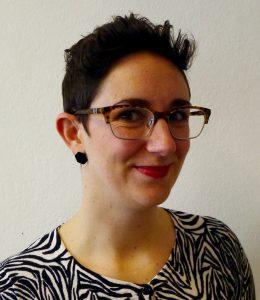 Eine lächelnde Frau mit sehr kurzen dunklen Haaren, Schildkröten-Schale umrandete Brille, eine Nase Piercing und eine Zebra gemusterte Strickjacke.