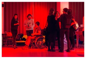 Image description: in a room with a red glowing light, seven people in two groups chatting to each other with drinks in their hands. Some people are standing while another sits in a wheelchair.