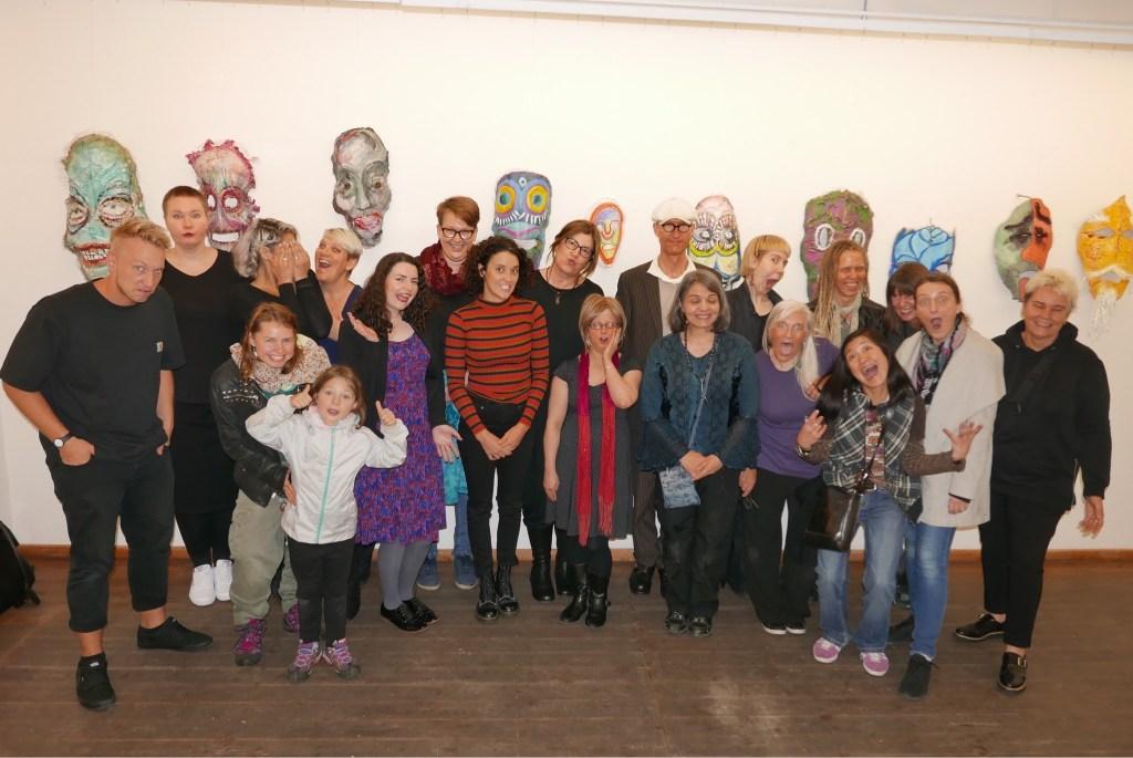 Gruppenfoto mit bunten Masken in der Rückwand