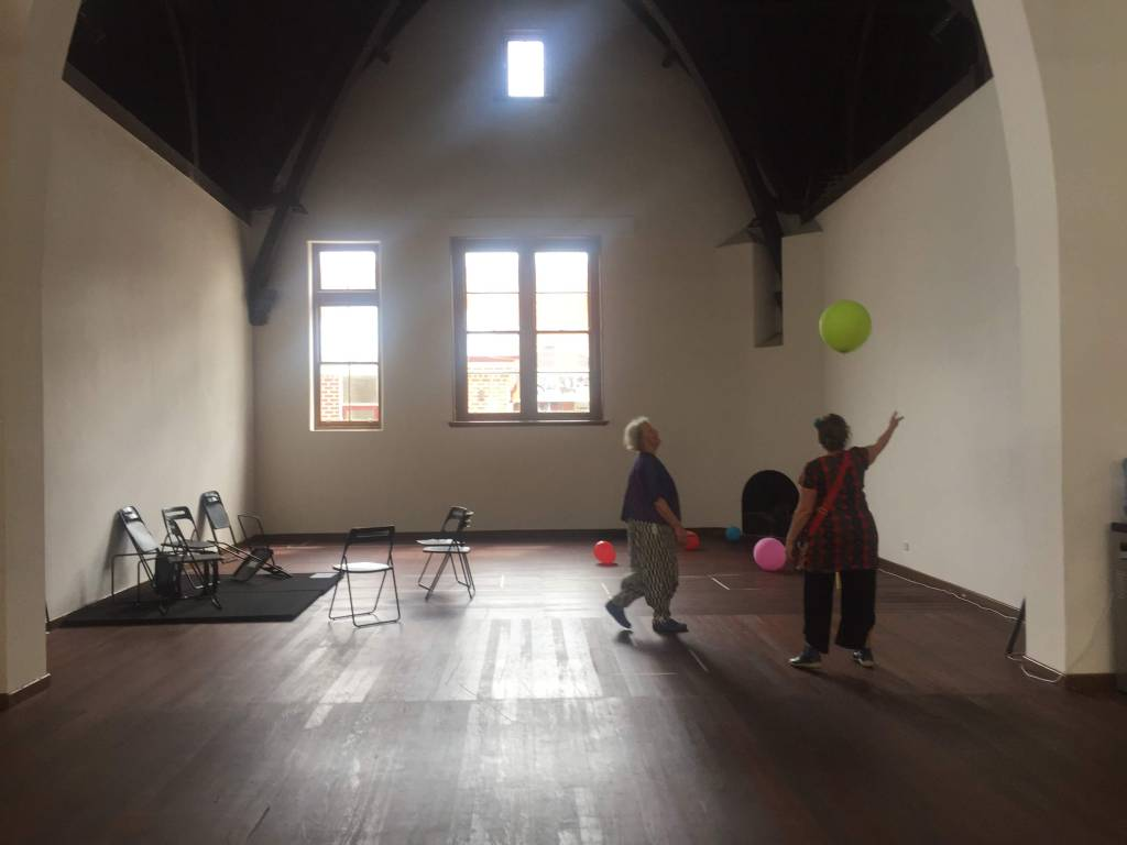 Two people in a room with chairs playing with colorful balloons