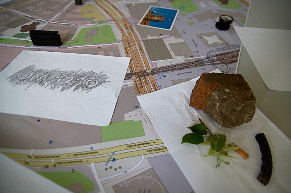 city map with rubbing drawings, a stone, leaves, a postcard and a cigarette butt