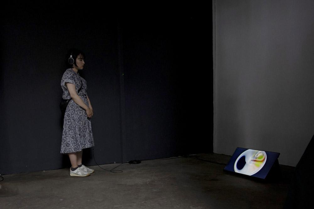 Person mit Kopfhörern in einem dunklen Raum schaut auf einem Monitor auf dem Boden.