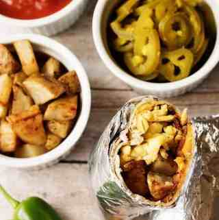 A hearty and filling make ahead breakfast burrito recipe with bacon, eggs, potatoes, and cheese wrapped in a warm tortilla.