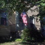 photo of porch with flag under tree