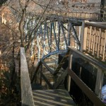 Photo of wooden steps next to arched bridge.