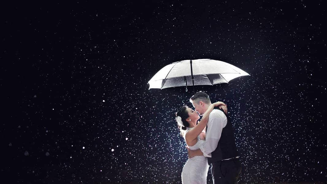 Bride and groom kissing rain thunderstorm umbrella