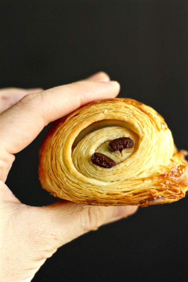 chocolate croissant in hand