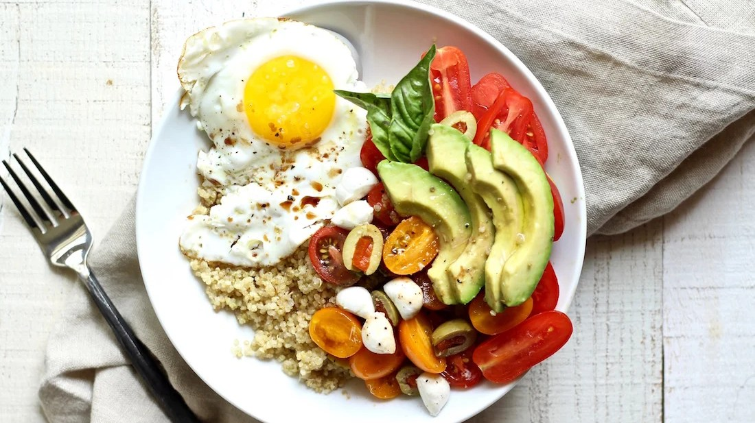 easy quinoa breakfast bowl with fried eggs and avocado