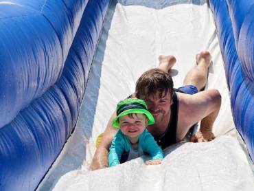 Dad and son sliding down water slide together