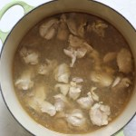 Chicken simmering in chicken bone broth for avgolemono soup recipe