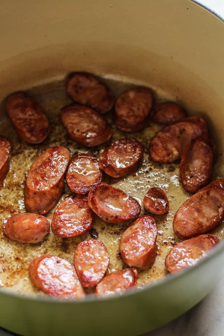 Cajun Sausage sauteeing in dutch oven for Thai pumpkin butternut squash soup
