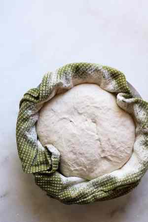 Sourdough Bread fermenting in a salad bowl with a kitchen towel