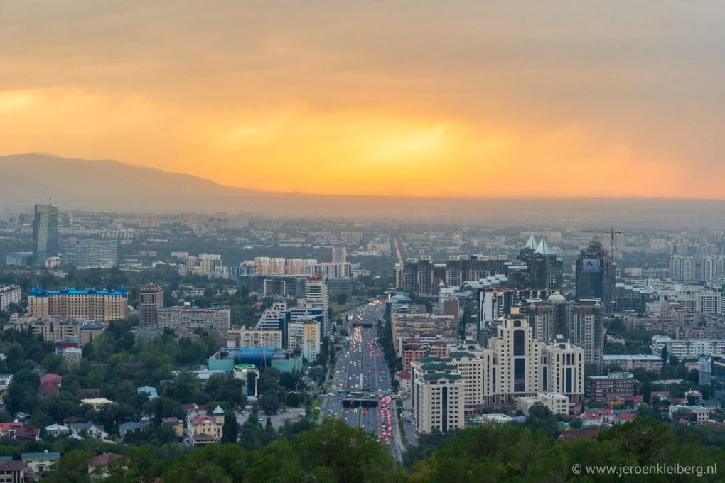 An orange sun lights the evening sky above Almaty