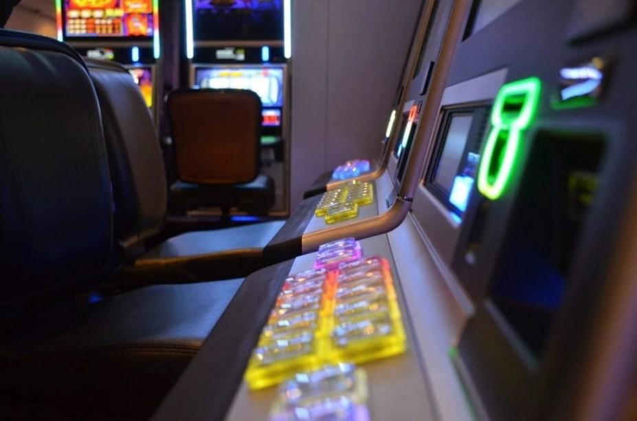 Glücksspielautomaten aufgereiht in einer Spielothek.